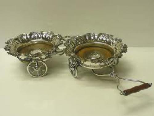 A decorative antique silver plated decanter waggon with articulated movement 